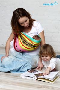 Новорожденный ребенок в слинге с кольцами